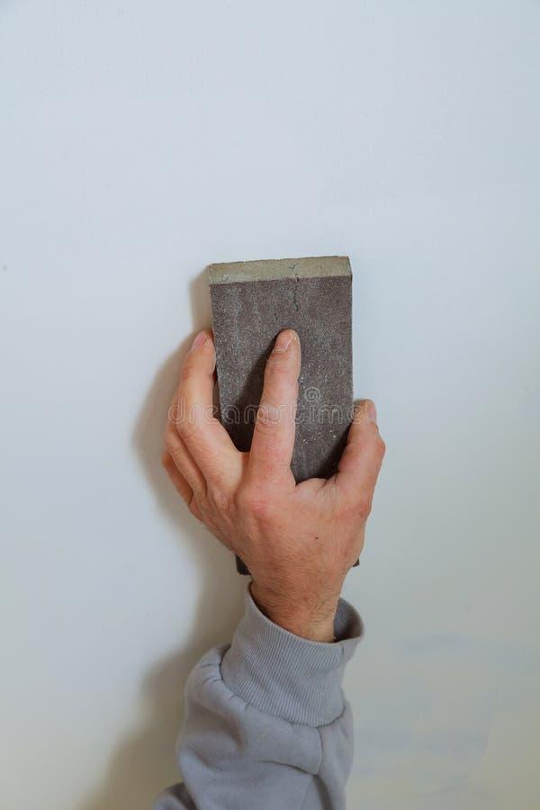 Le plâtrier principal lisse les coutures avec le plâtre entre les panneaux de plâtre sur le mur Panneau de gypse sous forme de va images libres de droits