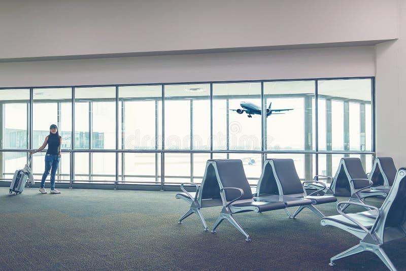 Le plan et le sac à dos de femme de voyageur voient l'avion photo stock