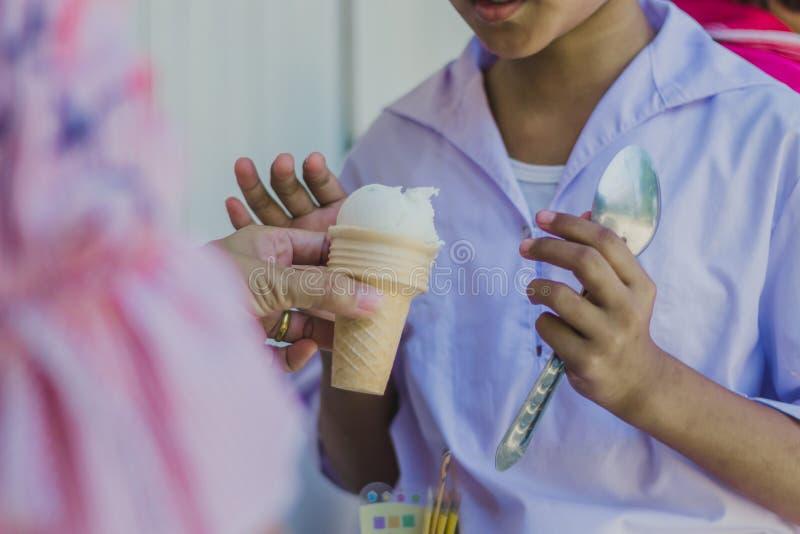 Le plan rapproché aux mains du ` s de professeur donnent la crème glacée aux étudiants photos stock