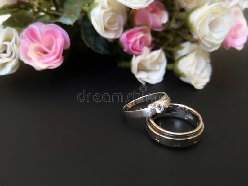 Le plan rapproché avec des anneaux de mariage et les belles roses fleurissent le fond photographie stock libre de droits