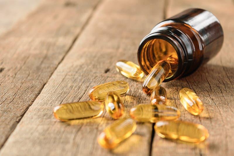 Le plan rapproché complète la bouteille de vitamines sur le fond en bois image libre de droits