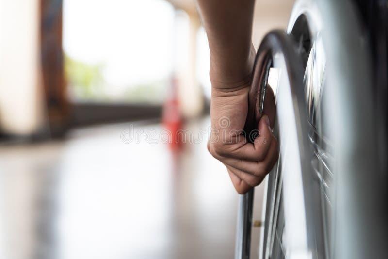 Le plan rapproché a désactivé la main d'homme sur la roue du fauteuil roulant image stock