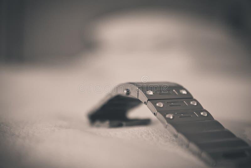 Le plan rapproché d'un bracelet de montre en métal est sur un tissu blanc image libre de droits