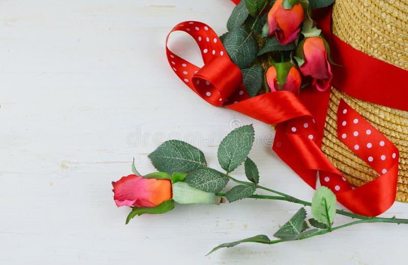 Le plan rapproché d'un chapeau de paille étant décoré des rubans et des roses rouges sur un blanc a lavé le fond en bois rustique image stock