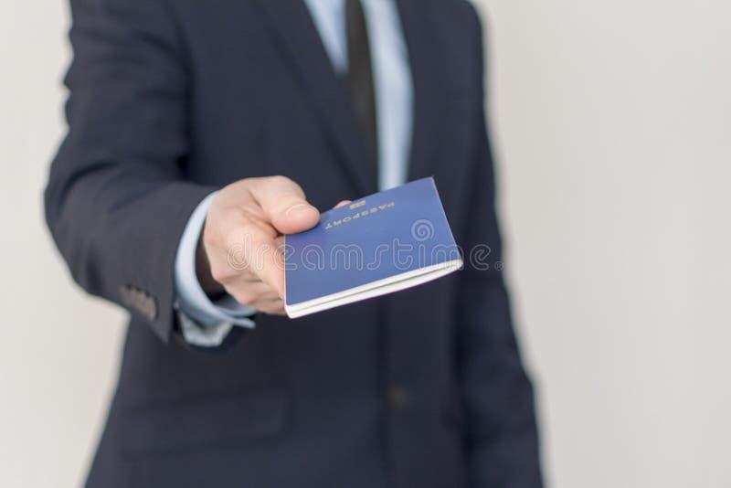 Le plan rapproché d'un homme d'affaires donnent pour l'inspection son passeport photos libres de droits