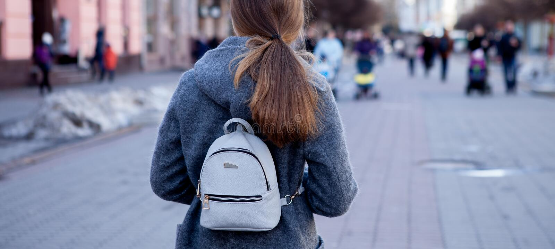Le plan rapproché d'une belle fille de brune avec de longs cheveux dans un manteau circule la ville au printemps, vue par derrièr photo libre de droits