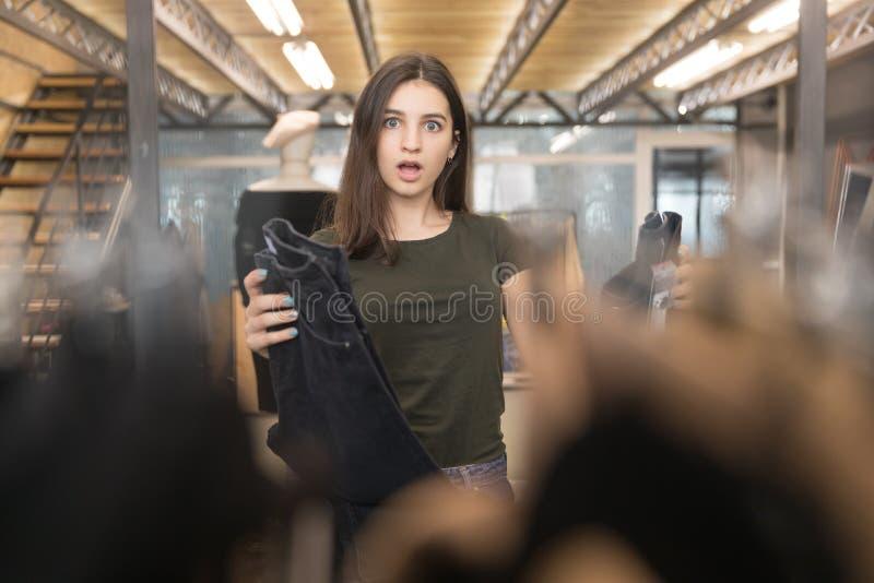 Le plan rapproché d'une fille choisit les jeans noirs dans le magasin photo libre de droits