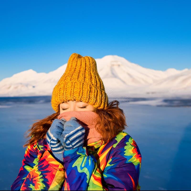 Le plan rapproché d'une fille dans une veste et un jaune d'arc-en-ciel a tricoté le chapeau sur le fond le Svalbard Longyearbyen  image stock