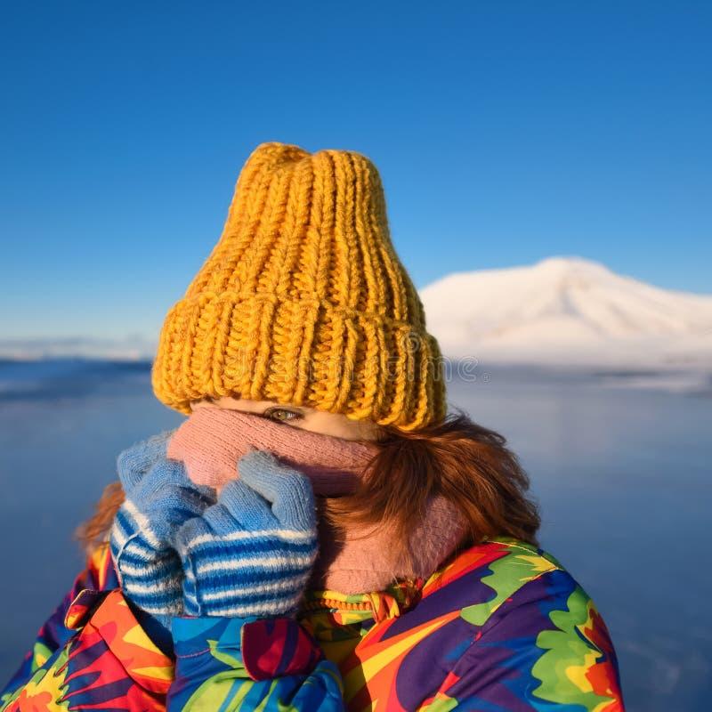 Le plan rapproché d'une fille dans une veste et un jaune d'arc-en-ciel a tricoté le chapeau sur le fond le Svalbard Longyearbyen  image libre de droits