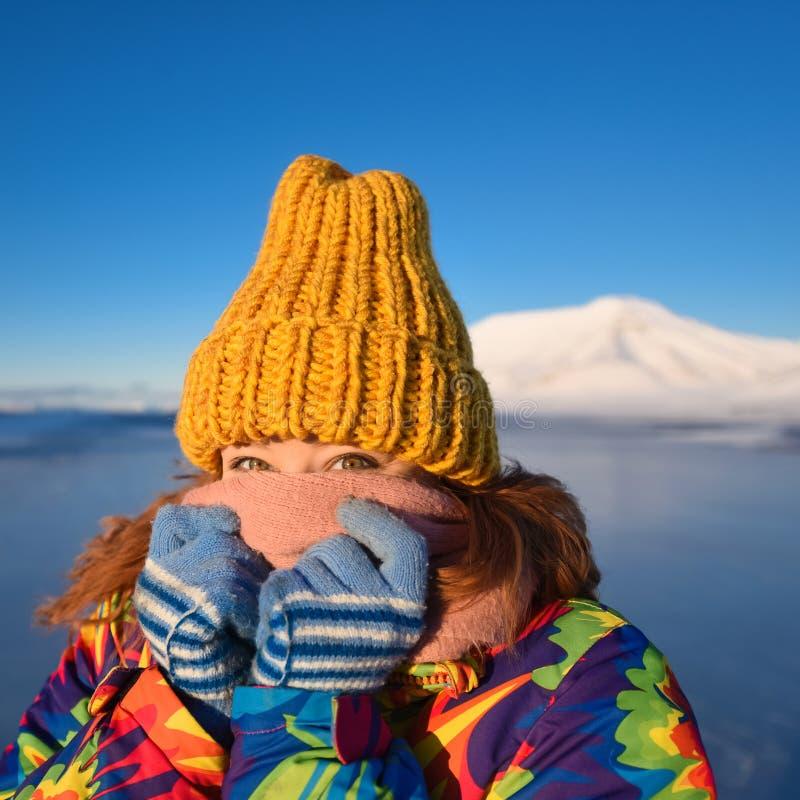 Le plan rapproché d'une fille dans une veste et un jaune d'arc-en-ciel a tricoté le chapeau sur le fond le Svalbard Longyearbyen  photographie stock libre de droits