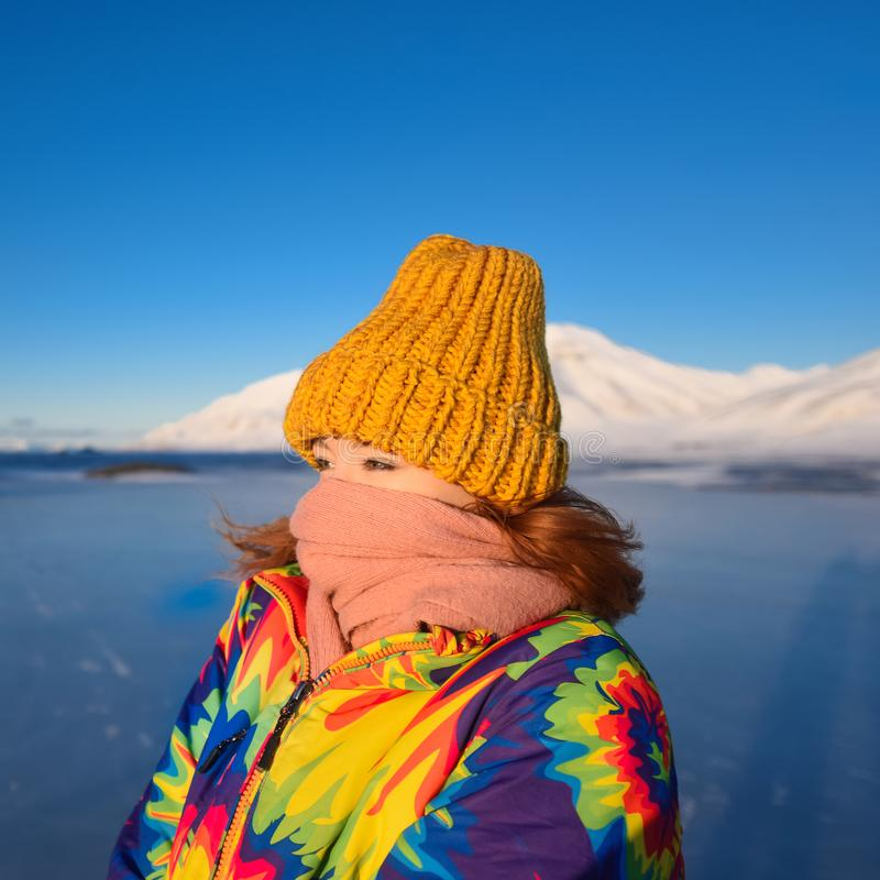 Le plan rapproché d'une fille dans une veste et un jaune d'arc-en-ciel a tricoté le chapeau sur le fond le Svalbard Longyearbyen  photos libres de droits