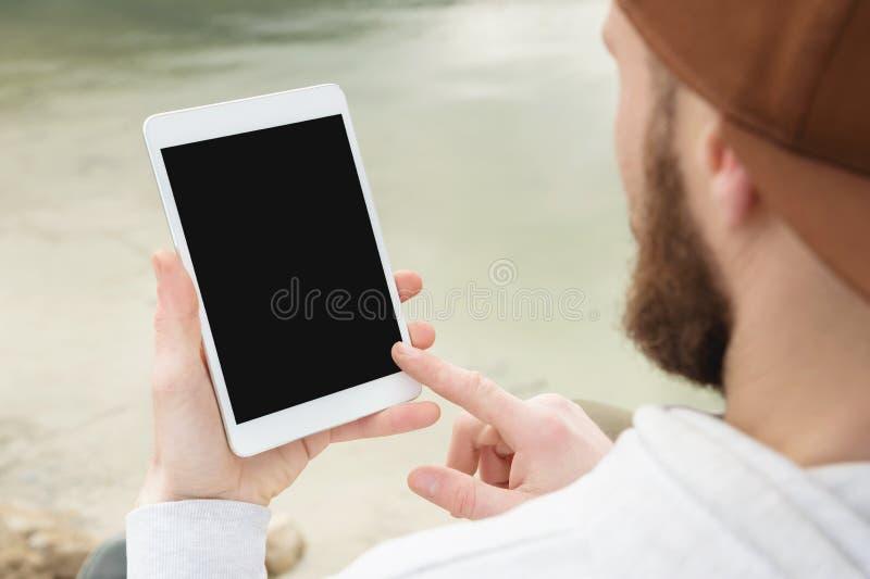 Le plan rapproché d'une horde dans un chapeau brun tient en plein air un PC blanc de comprimé dans des ses mains Un homme barbu r images stock