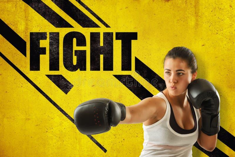 Le plan rapproché de culture de la jeune femme dans la participation une de gants de boxe distribuent, contre le mur jaune avec l photos stock
