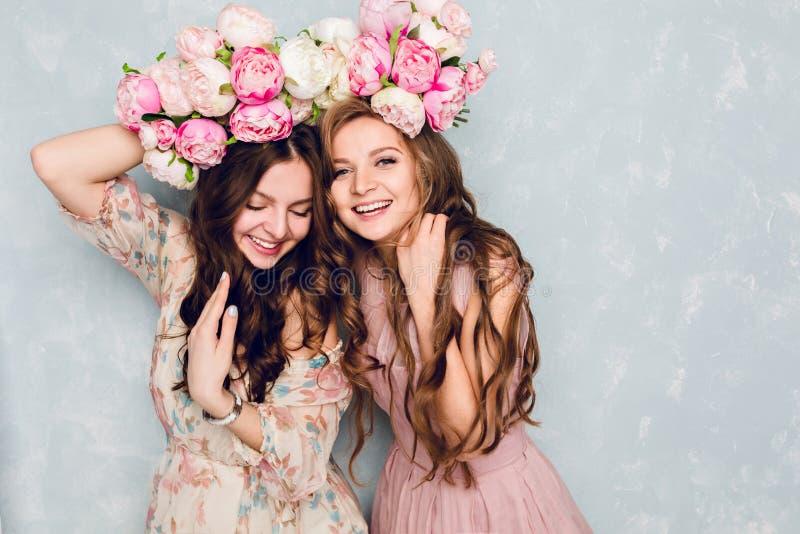 Le plan rapproché de deux belles filles se tiennent dans un studio, qui jouent idiot avec des anneaux des fleurs sur leurs têtes  images stock
