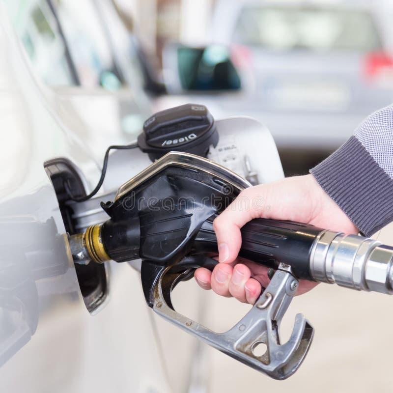Le plan rapproché de homme le carburant de pompage d'essence de main dans la voiture à la station service photo libre de droits