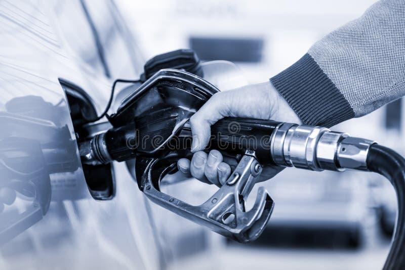 Le plan rapproché de homme le carburant de pompage d'essence de main dans la voiture à la station service photos libres de droits