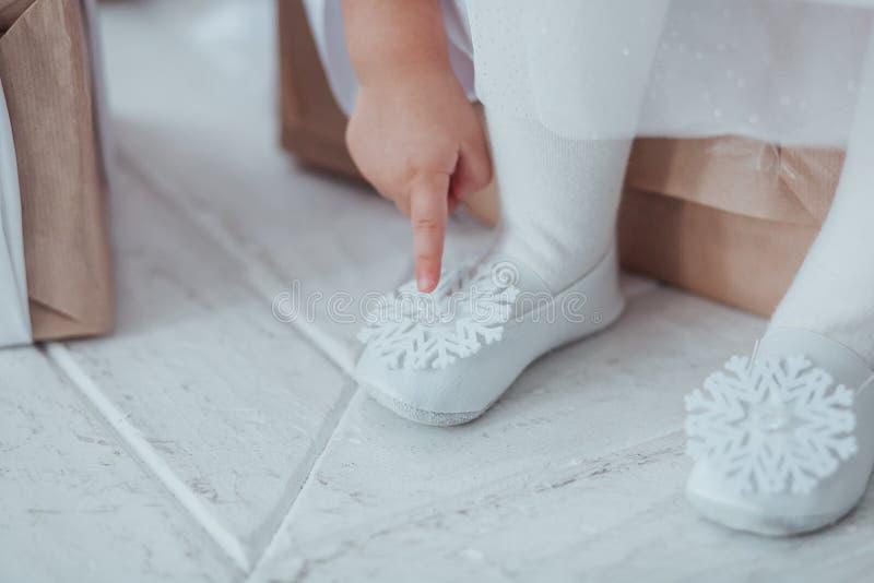 Le plan rapproché de jeunes jambes de ballerine, se reposent dans des chaussures de pointe avec le décor de flocon de neige au fo photo libre de droits
