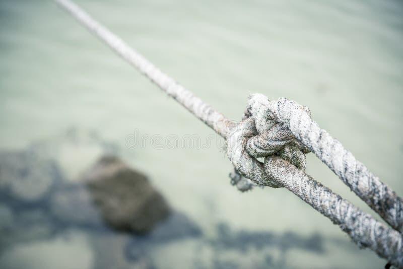 Le plan rapproché de l'a étroitement attaché le noeud avec une corde blanche attachée par un pêcheur images libres de droits