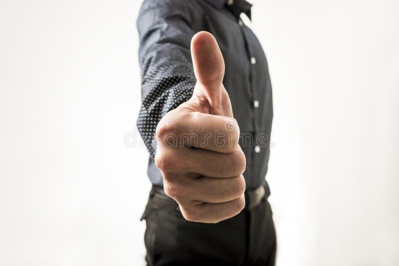 Le plan rapproché de l'homme d'affaires montrant des pouces lèvent le signe vers vous image libre de droits
