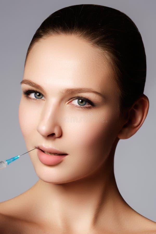 Le plan rapproché de la belle femme obtient l'injection dans des ses lèvres Pleines languettes photo libre de droits