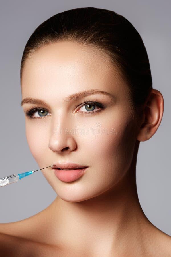 Le plan rapproché de la belle femme obtient l'injection dans des ses lèvres Pleines languettes images stock