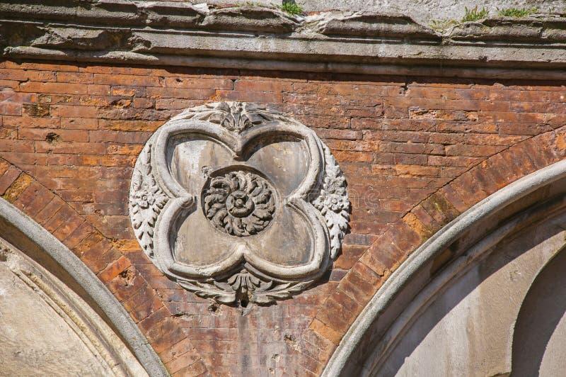 Le plan rapproché de la brique a fait la façade d'un vieux bâtiment avec l'ornement de marbre de relief à Ferrare images stock