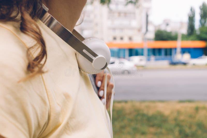 Le plan rapproché de la femme avec des écouteurs circule la ville dans la somme photo stock