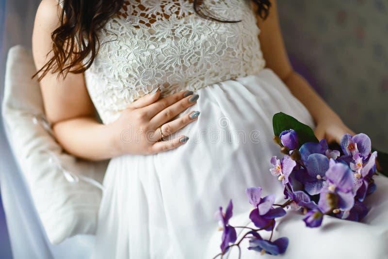 Le plan rapproché de la femme enceinte méconnaissable avec remet le ventre ? n un blanc a lacé le peignoir, arc blanc sur le vent photographie stock