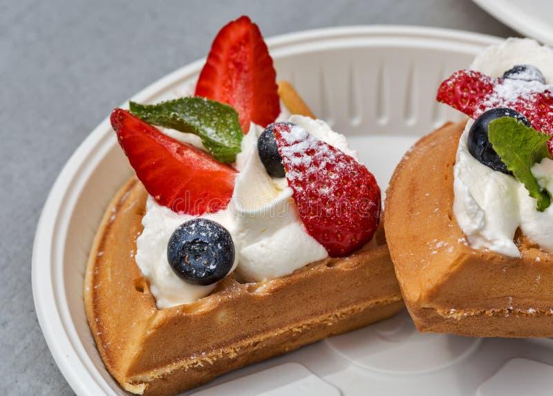 Le plan rapproché de la fraise, la myrtille et la crème durcissent photographie stock libre de droits