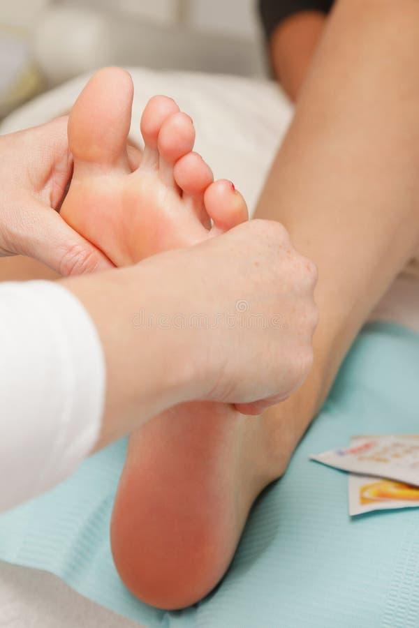 Le plan rapproché de la jeune femme obtient le massage de pied photos stock
