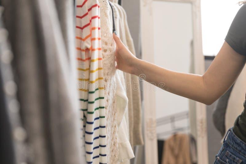 Le plan rapproché de la main d'une fille se tient sur les vêtements accrochants dans le magasin images stock
