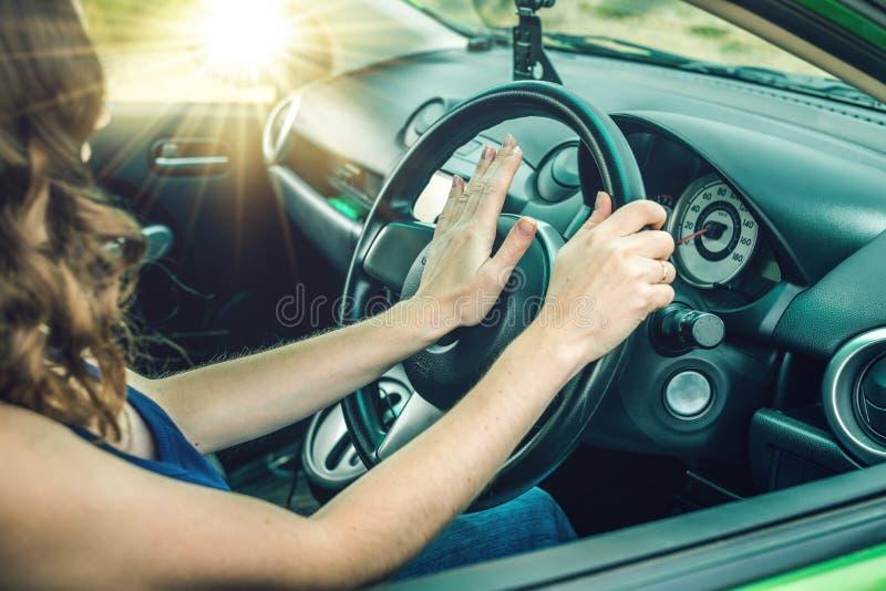Le plan rapproché de la main femelle sur le volant appuie sur le bouton de klaxon dans la voiture Irritation de concept tout en c photo libre de droits
