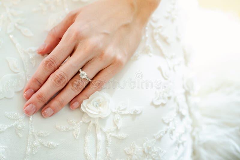Le plan rapproché de la main de la fille porte un anneau sur le doigt d'anneau gauche Mettez vos mains sur la robe de mariée blan photos stock