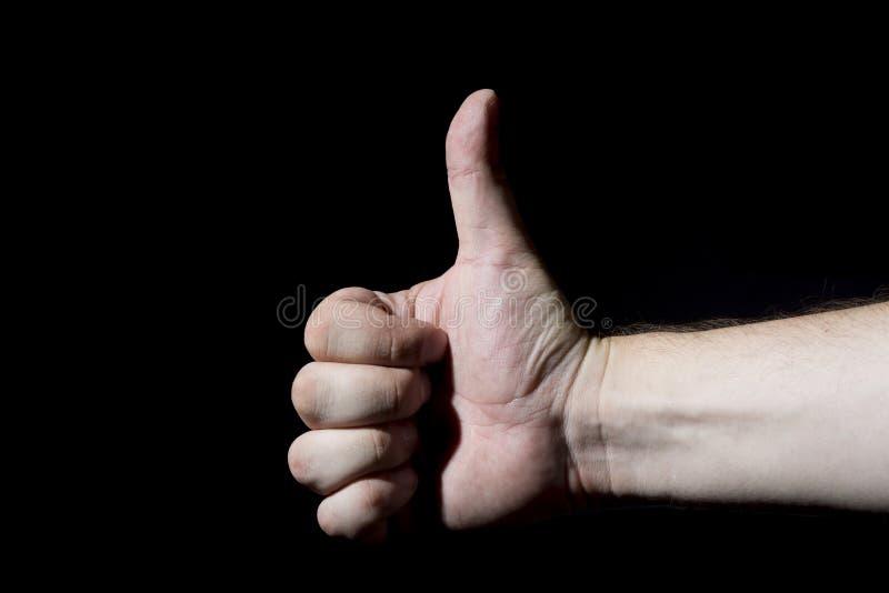Le plan rapproché de la main masculine montrant des pouces lèvent le signe contre le noir photo stock