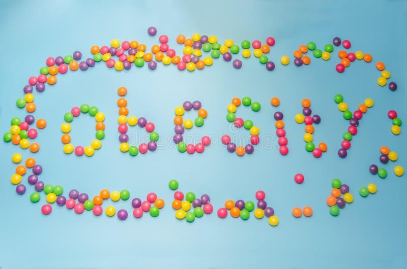 Le plan rapproché de la sucrerie, sucre de caramel a enduit l'obésité, sur le backgrou bleu photographie stock