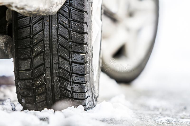 Le plan rapproché de la voiture roulent dedans le pneu d'hiver sur la route neigeuse photos stock