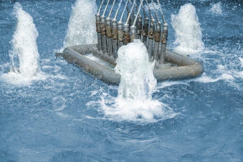 Le plan rapproché des becs de fontaine avec jet d'eau et éclabousse Geysers d'Aqua dans la piscine des usines hydrauliques photo stock
