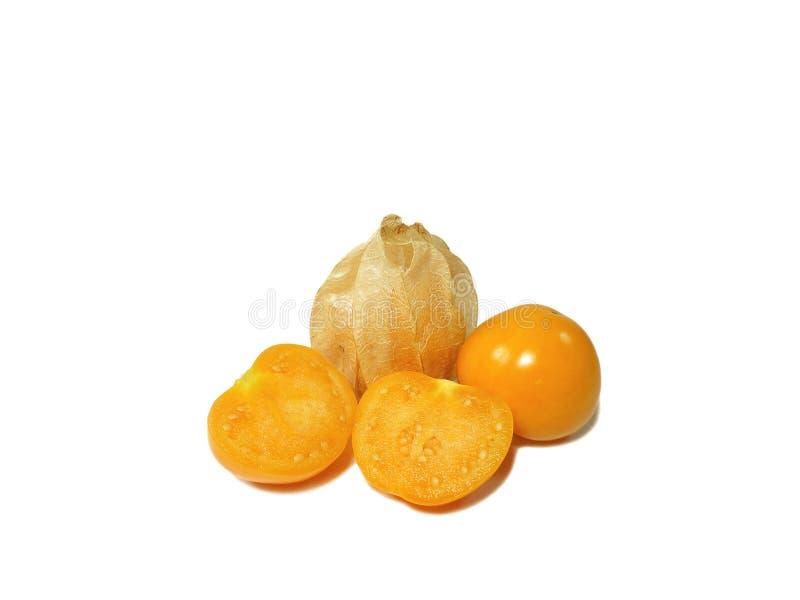 Le plan rapproché des coquerets comestibles mûrs jaunes lumineux, un avec le calice, un entier, un a coupé dans la moitié photographie stock libre de droits