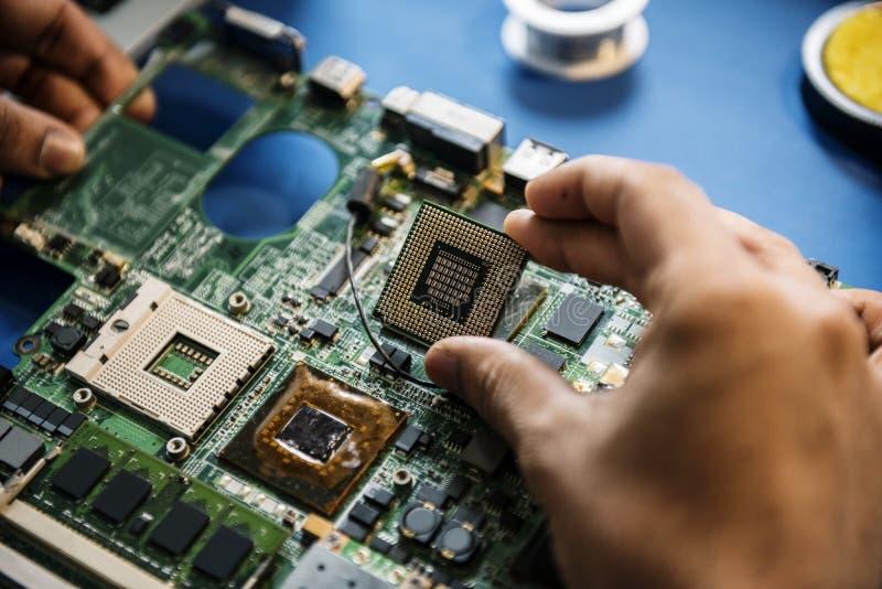 Le plan rapproché des mains avec l'électronique de microprocesseur de mainboard d'ordinateur partie image libre de droits