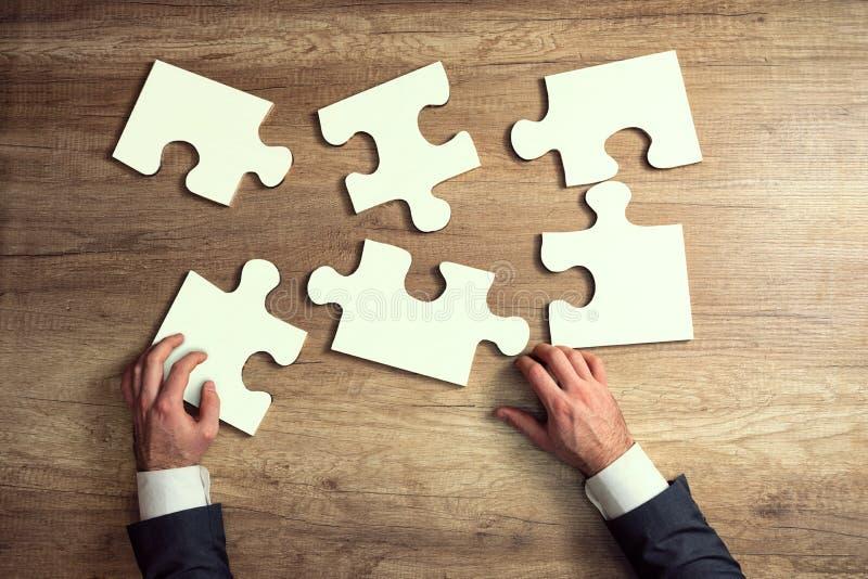 Le plan rapproché des mains d'homme d'affaires essayent à accomplir le puzzle denteux images libres de droits