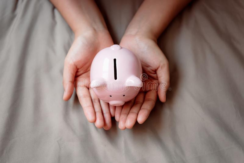 Le plan rapproché des mains de femme tient la tirelire sur le fond de tissu, les opérations bancaires économisantes d'argent et d image stock