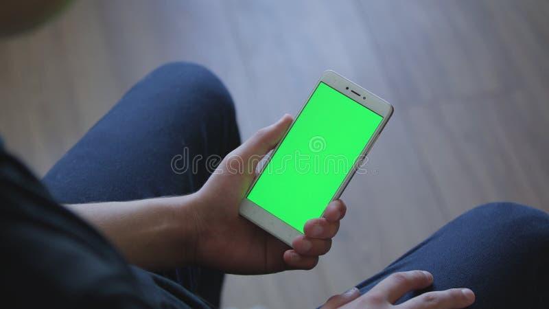 Le plan rapproché des mains masculines tenant le téléphone intelligent avec l'écran vert prekeyed pour des effets Réservation mob photo libre de droits