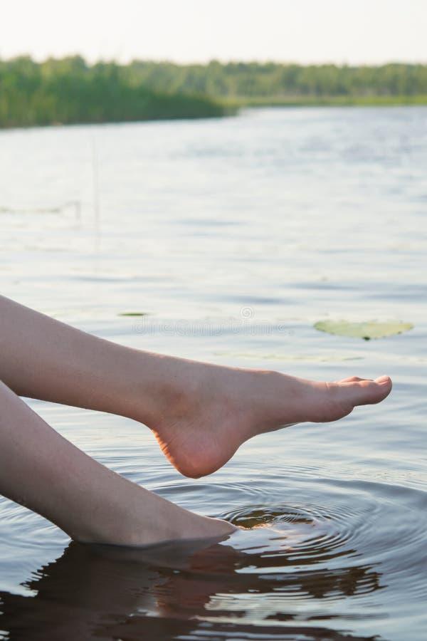 Le plan rapproché des pieds a plongé dans un lac bleu image stock