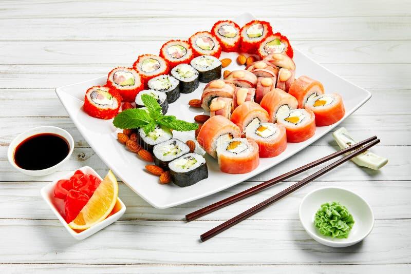 Le plan rapproché des sushi japonais traditionnels a placé avec des saumons et des thons sur le fond blanc Conception de menu de  image stock