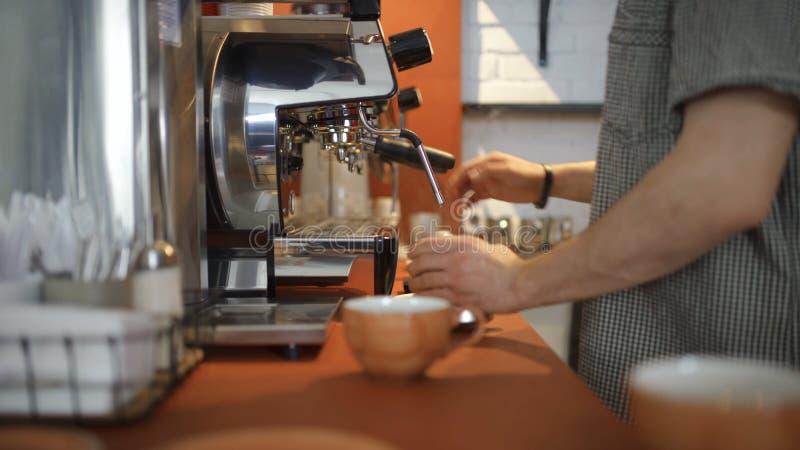 Le plan rapproché du barman professionnel verse le café de la machine de café Art Maîtrise dans la gestion de l'équipement de caf images libres de droits