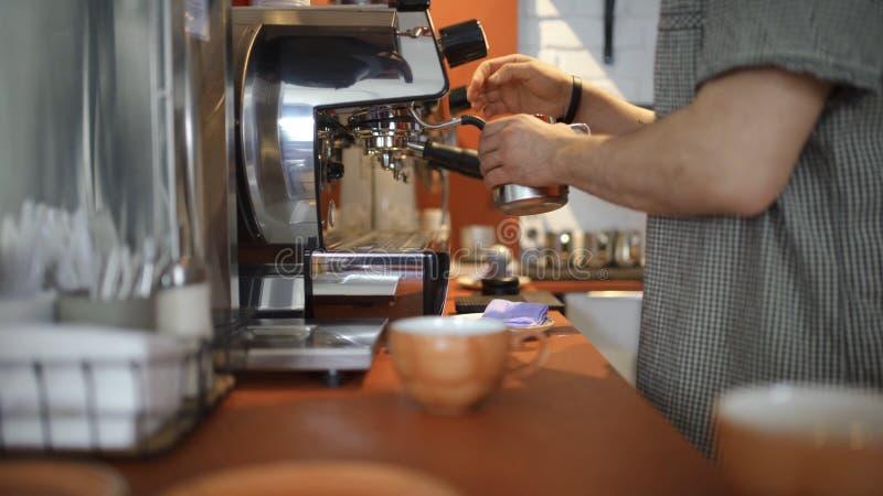 Le plan rapproché du barman professionnel verse le café de la machine de café Art Maîtrise dans la gestion de l'équipement de caf photographie stock libre de droits
