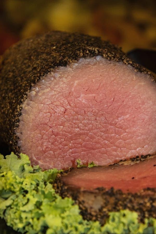 Le plan rapproché du boeuf de rôti rare juteux custed avec le poivre coupé en tranches avec de la laitue verte bouclée garnissent photos stock