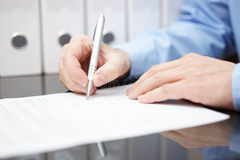 Le plan rapproché du bussinessman signe le contrat avec la documentation i photos libres de droits