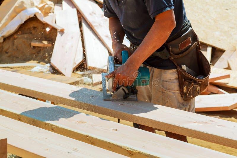 Le plan rapproché du charpentier employant une circulaire a vu pour couper un grand panneau de bois photographie stock libre de droits