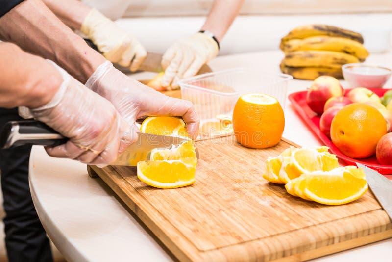 Le plan rapproché du chef faisant cuire le cuisinier de coupe de restaurant de cuisine de nourriture remet à homme d'hôtel la pré photos libres de droits